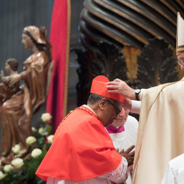 Image: Pope Francis gives the traditional biretta hat to new cardinal Anthony Soter Fernandez of Malaysia during a consistory ceremony to install 17 new cardinals in Saint Peter's Basilica at the Vatican