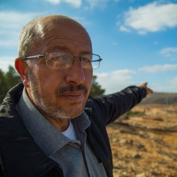 Image: Ibrahim Yacoub, points to DzAmonadz, the Israeli settlement