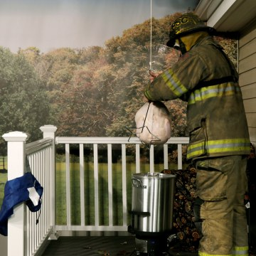 Image: Firefighter prepares to drop a Thanksgiving frozen turkey into a deep fryer