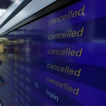 A passenger walks past a flight information board showing cancelled flights during a pilots strike of German airline Lufthansa at  Frankfurt airpor