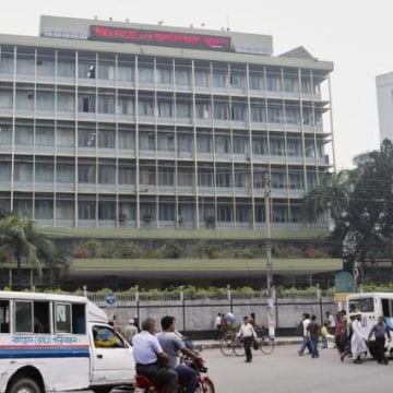 Commuters pass by the front of the Bangladesh central bank building in Dhaka