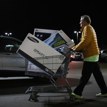 Image: Shoppers exit a Best Buy after purchasing electronic items during Black Friday sales in San Diego