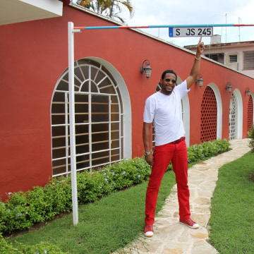 Former Olympian Javier Sotomayor stands under a custom high-jump bar outside his home, which stands at 2.43 meters -- his world record.