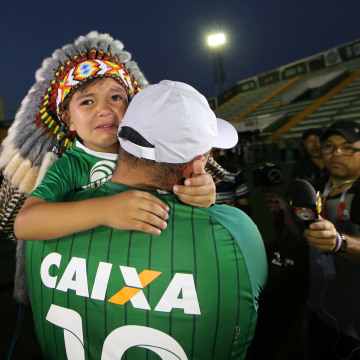 Image: A fan of Chapecoense soccer team and his son react at the Arena Conda stadium in Chapeco