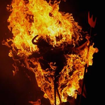 A figure representing the Devil burns on