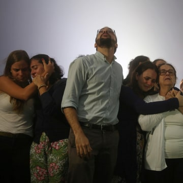 Image: Relatives of Brazilian journalist Guilherme Marques mourn during a mass in Rio de Janeiro
