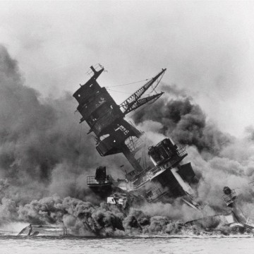 Image: The battleship USS Arizona belches smoke as it topples over into the sea.