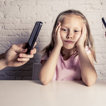 Image: A child sits between two people holding phones