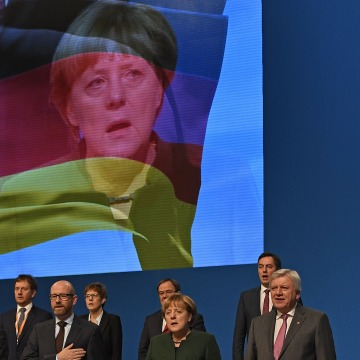 Image: CDU leaders including Angela Merkel, second right, sing the national anthem at the party conference in Essen, Germany.