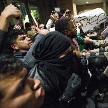 Law enforcement officers push protesters out of the Texas A&M University student center