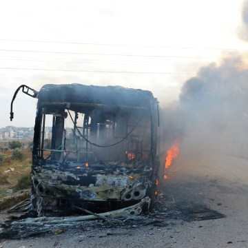 Image: A man on a motorcycle drives past burning buses