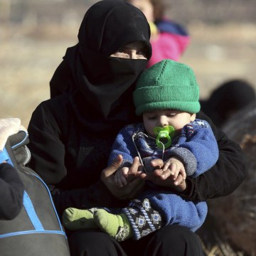 Image: A Syrian woman holding a child who were  evacuated from the embattled Syrian city of Aleppo