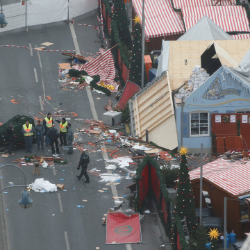 Image: Policemen investigate the scene where a truck ploughed into a crowded Christmas market in the German capital last night in Berlin