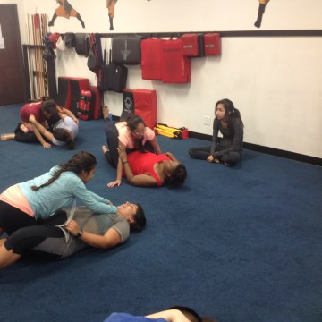 Participants from Gomez' self-defense workshop practice top mount attack positions with a choke hold. The exercise involved working on controlled escapes.