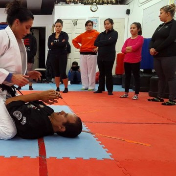 A student performs a role as an attacker exerting a chokehold on instructor Maurice Gomez.