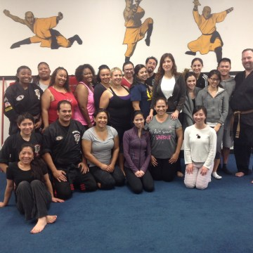 Owner of MG Kenpo Academy Maurice Gomez (bottom row, left) with a group of women enrolled in one of his self-defense workshops in Duarte, California.