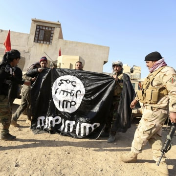 Image: Iraqi army soldiers celebrate with seized ISIS flag