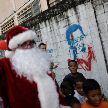 Image: Santa Claus walks past a mural depicting Venezuela's late President Hugo Chavez during a visit to residents of the slum of Petare in Caracas