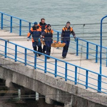 Image: Russian rescuers carry a stretcher with a body