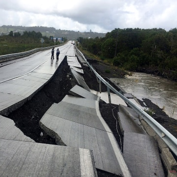 Image: A damaged road is seen after a quake at Tarahuin, on Chiloe island, southern Chile