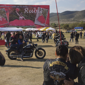 Image: A couple, who traveled from Mexico City with a group of bikers, pose for a photo at Rubi's quinceanera