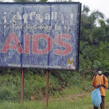 Image: A man stands next to an AIDS billboard as he cleans a street in Yaounde