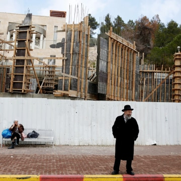 Image: Israelis are seen near a construction site in the Israeli settlement of Ramat Shlomo, in the occupied West Bank