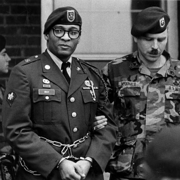Image: Ronald A. Gray in handcuffs and chains, escorted by military police leaving a Fort Bragg, N.C.