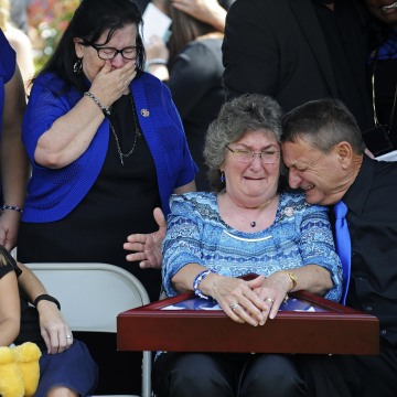 Image: Parents of East Baton Rouge Sheriff deputy Brad Garafola weep after being presented with a flag
