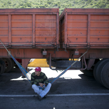 In this Nov. 14, 2016 photo, a truck driver rests on his hammock under his truck as he waits to enter the port in Puerto Cabello, Venezuela.
