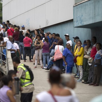 In this Nov. 18, 2016 photo, people wait outside a supermarket to buy government subsided food in Caracas, Venezuela.