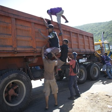 In this Nov. 14, 2016 photo, young men climb into an empty food truck, in search of leftover grain, as the vehicle comes to a slow stop outside the port in Puerto Cabello, Venezuela.