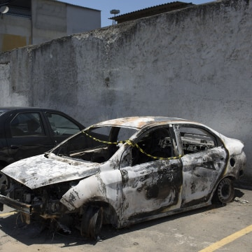 Image: A burned car sits in the parking lot of the police station in Belford Roxo, Brazil