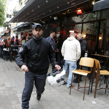 Image: Israeli policemen runs at the scene of a shooting incident in Tel Aviv, Israel