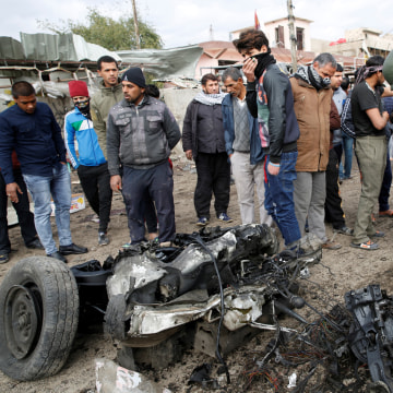 Image: People gather around a wrecked vehicle