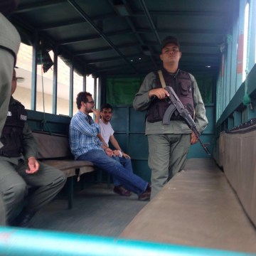 Venezuelan activist Francisco Marquez and colleague Gabriel San Miguel, sit in the back of a truck shortly after being stopped at a security checkpoint by the Venezuelan National Guard