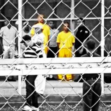 Venezuelan activists Francisco Marquez, left, and Miguel San Miguel, right, in yellow, stand outside the July 26 prison in San Juan de los Morros, Venezuela