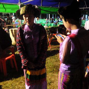 Image: Teenagers in traditional dress use their smartphones in Myanmar
