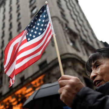 Image: A women holds an American flag while protesting outside Trump Tower during a demonstration organized by the New York Immigration Coalition against President-elect Donald Trump in the Manhattan borough of  New York