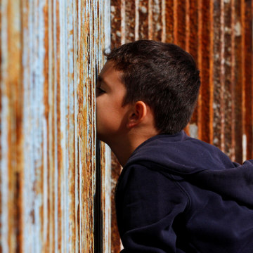 Image: A boy talks to his relatives across a fence separating Mexico and the United States, in Tijuana