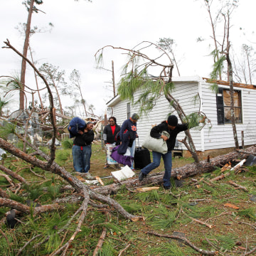 Image: Richardson, Daly, Vaughn and Furlow remove belongings from their home after a tornado struck the residential area on Sunday in Albany
