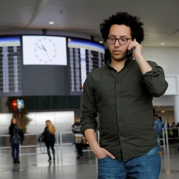 Image: Mark Doss, Supervising Attorney for the International Refugee Assistance Project at the Urban Justice Center speaks on his cell phone at John F. Kennedy International Airport in Queens, New York, U.S.