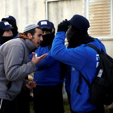 Image: A pro-settlement activist argues with an Israeli policeman