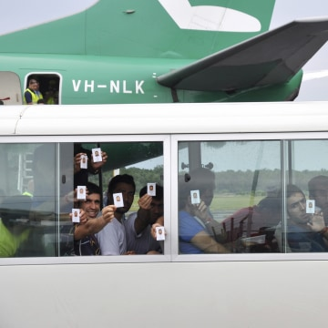 Image: A group of asylum seekers hold up their identity after landing in Manus Island, Papua New Guinea