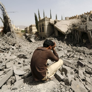 Image: Guard sits on the rubble of the house of Brigadier Fouad al-Emad, an army commander loyal to the Houthis, after air strikes destroyed it in Sanaa, Yemen