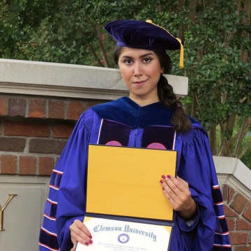 Image: Nazanin Zinouri poses for a photo with her PhD degree from Clemson University in Clemson, South Carolina.