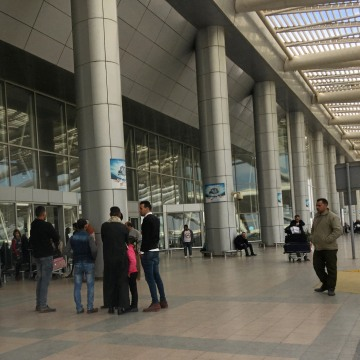 Image: People wait outside a Cairo airport terminal