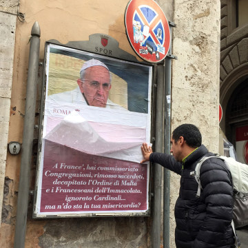 Image: A passerby lifts a paper sheet covering an anti-Pope Francis poster to read it, in central Rome, Italy, Feb. 4, 2017.