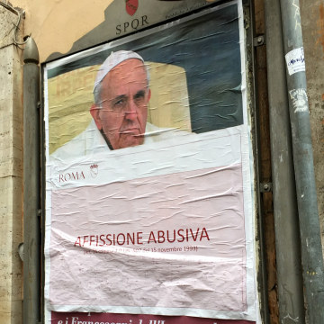"""Image: A paper sheet with writing in Italian reading """"Illigal Posting"""" covers an anti-Pope Francis poster in central Rome, Italy, Feb. 4, 2017."""