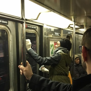 Image: Passengers scrub anti-Semitic graffiti off of a New York City Subway car
